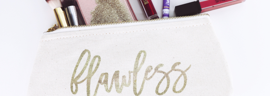 A Makeup bag in white canvas with flawless scrawled across in gold lettering. Makeup brushes, lipgloss, and pencils spill out