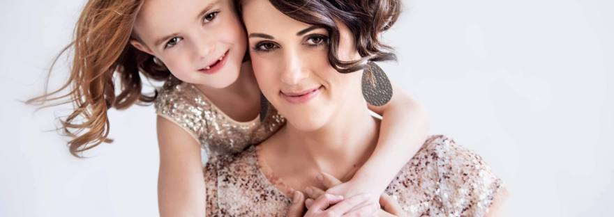 young girls stands behind her mom with arms wrapped around her as they both smile towards th photographer